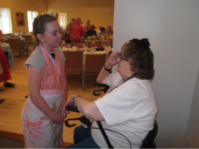 "McKenzie, 11. Helping at ""tea,"" a gathering of girl scouts at a UU congregation who served tea, sandwiches, dessert, and talked with guests."